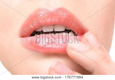 Woman with cold sore touching lips, closeup