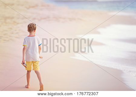 back view of little boy walking at the beautiful beach by the water at sunset