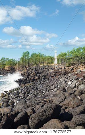 Kawaihae lighthouse on rocky Kamuela Hawaii shoreline surrounded by kiawe scrub built in 1915 of concrete.
