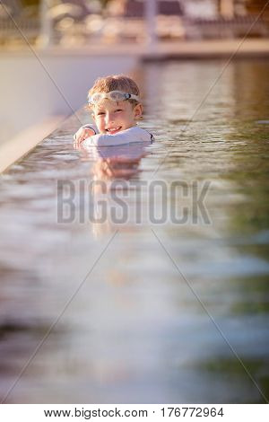 happy smiling boy in goggles enjoying infinity pool at nice resort during summer tropical vacation