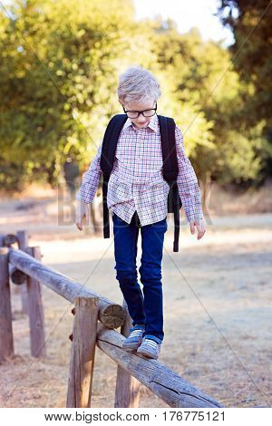 adorable little schoolboy with backpack being playful in the park ready for school year back to school concept