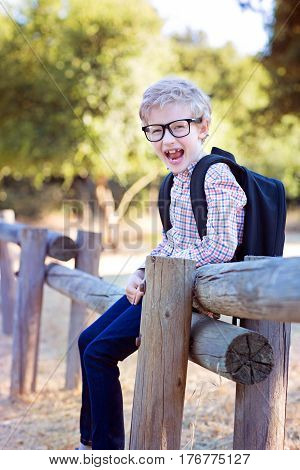 smiling little schoolboy with backpack being playful in the park ready for school year back to school concept