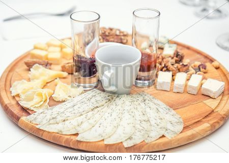 Different Delicious Cheeses On Wooden Round Board