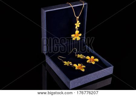 Chain with pendant and earrings in a blue box on a black background