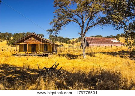 Old Boarded Up Farm House With Barn In Background
