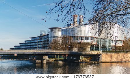 STRASBOURG FRANCE - DEC 25 2015: View through trees of the European Court of Human Rights building in Strasbourg France on a warm winter day and Ill river. ECHR is a international court established by the European Convention on Human Rights.