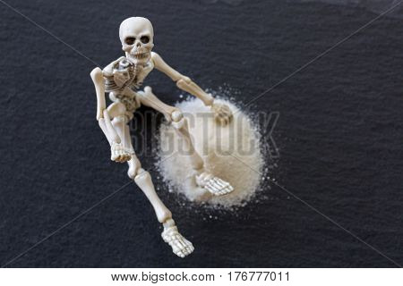 Soft focus white skeleton dead body bones sitting next to dangerous white fine powder like cocaine on black stone background