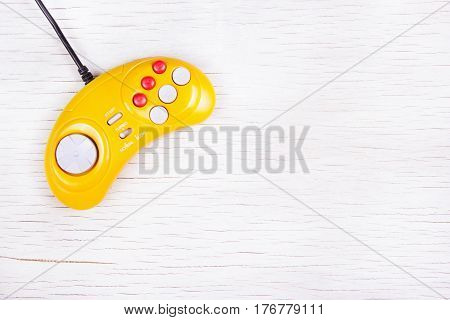 Video game console GamePad on a white wooden table. Yellow retro GamePad. Copy space.