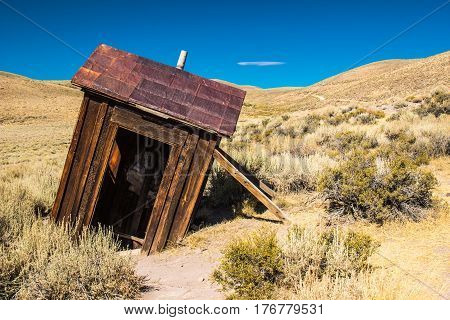 Wooden Outhouse Sinking In The Ground In Arizona Desert