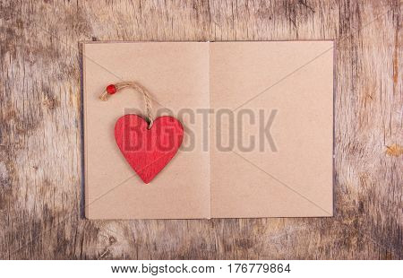 Red wooden heart and an open book with blank pages on the old wooden background. Bookmarks and Valentine of wood. Copy space
