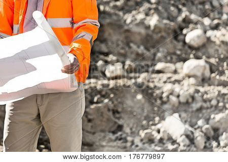 Midsection of supervisor holding blueprint at construction site
