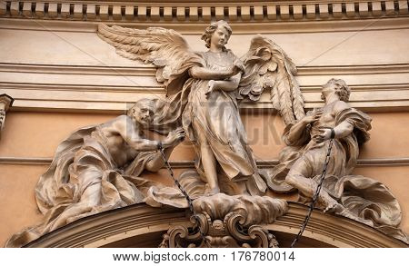 ROME, ITALY - SEPTEMBER 05: Statue of Angel about to free two slaves joined at the wrists by a real iron chain on facade of Santissima Trinita degli Spagnoli Church in Rome on September 05, 2016.