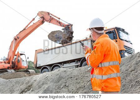 Side view of architect using walkie-talkie while working at construction site