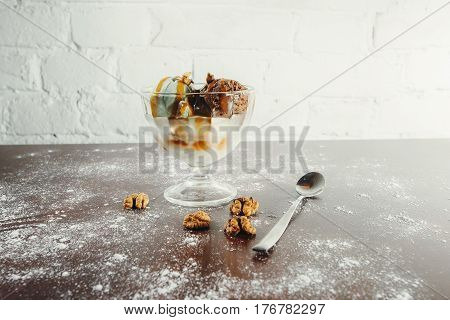 Homemade chocolate ice cream with peanut butter, sprinkle with chopped peanuts in a glass bowl, teaspoon on a wooden table, horizontal top view. Still life