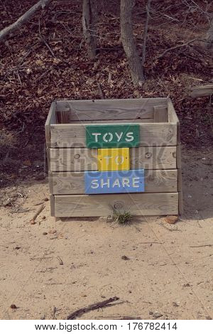 Wooden box set near the beach with toys.