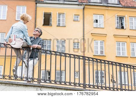 Low angle view of loving middle-aged couple by railing against building