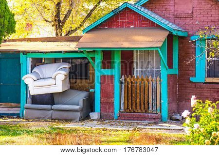 Brick Bugalow With Chair Stacked On Top Of Couch Outside