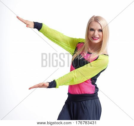 Attention here Cropped studio portrait of an attractive red lipped female in sportswear holding copyspace on the side in her hands smiling happily isolated