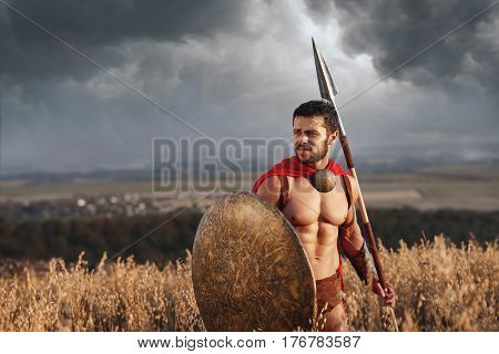 Warrior with beard and bare torso going in attack with bronze rounded shield and weapon. Athletic soldier in armor and helmet wearing like spartan. Dark clouds in sky. War in field.