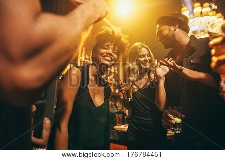 Image of happy young people having fun at disco. Group of friends enjoying a party at nightclub.