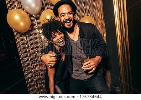 Portrait of happy young couple together at nightclub. Young people enjoying party.