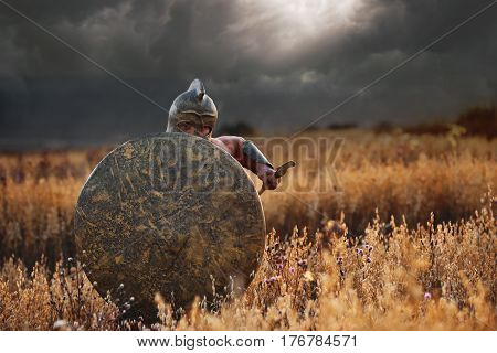 Front view of warrior going forward in attack. Soldier in armor and helmet like spartan holding bronze shield and sword front of himself. Nighttime and bad weather at field.