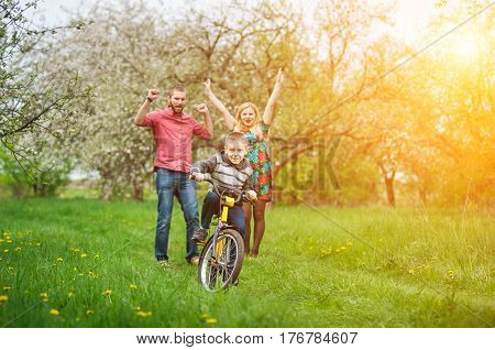 Young Parents Teaching His Son To Ride A Bike