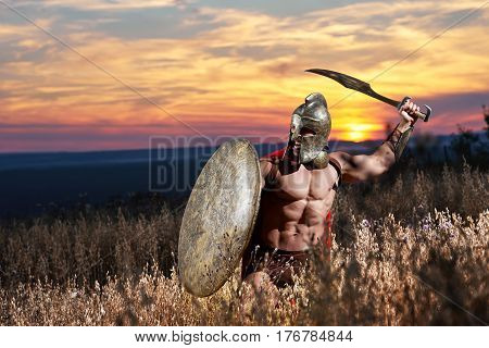 Warrior in helmet with bare torso wearing red cloak like spartan going in attack with iron sword. Incognito male like antique roman soldier holding bronze shield in hand. Sky at sunset.