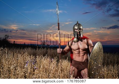 Athletic warrior man with bare torso wearing iron helmet and red cloak holding sword and standing among field at dark. Male wearing like spartan or antique roman soldier posing with shield.