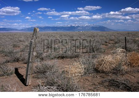 Fence post and barbed wire on the high plains of the San Luis Valley near Alamosa, Colorado in springtime.