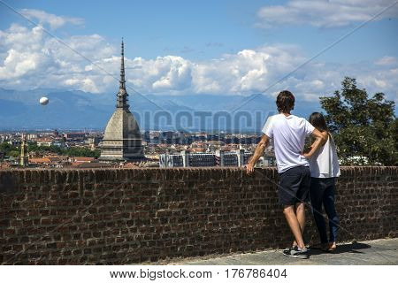 Panoramic view of Turin city center, in Italy, with couple admiring the view in a sunny day, with Mole Antonelliana and Alps in the background