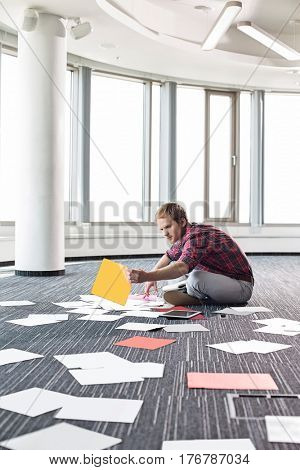 Businessman organizing photographs while sitting on floor at creative office