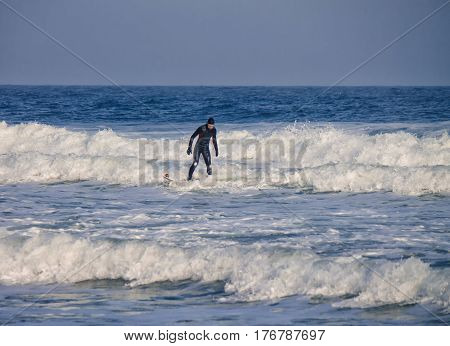 A surfer rides waves in the water wearing a wetsuit. Wave splash. waterproof suit
