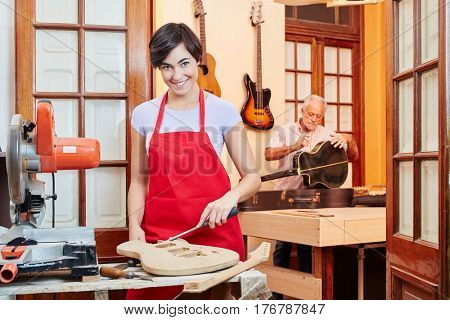 Young woman as apprentice in wood processing at guitar workshop
