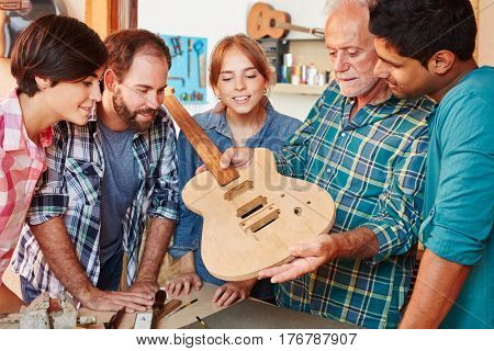 Team of apprentice and luthier in guitar lesson