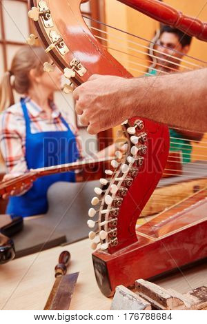 Luthier repairs harp in string instrument's workshop
