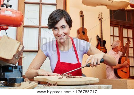 Woman as guitar maker trainee in wood apprenticeship