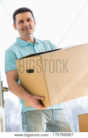 Man looking away while carrying cardboard box while entering new house