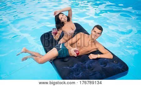 Beautiful Pair Floating On Mattress In Swimming Pool, Drinking Cocktails And Having Fun On Their Sum