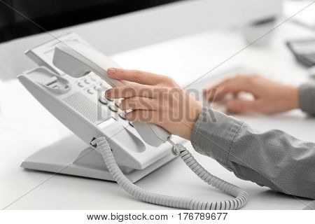 Woman picking up telephone receiver in office