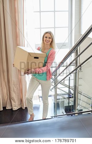 Smiling woman carrying cardboard box while moving up steps at new home