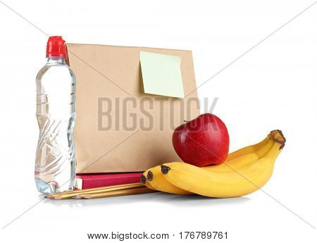 Paper lunch bag, bottle of water, fruits and stationery on white background