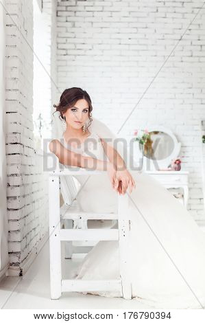 beautiful young fiancee sitting in a white room
