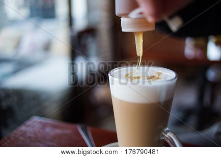 Close Up Image Of A Caffe Latte In A Coffee Shop With Natural Window Light Inside A Dark Interior
