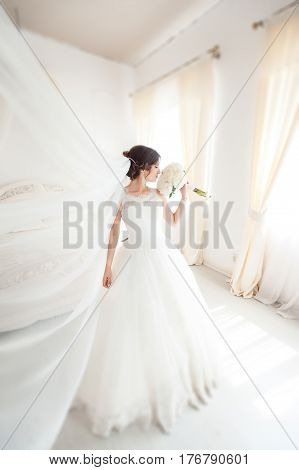 beautiful young fiancee standing in a white room sniffing wedding bouquet
