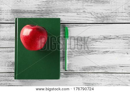 Exercise book with appetizing red apple and pen on wooden background