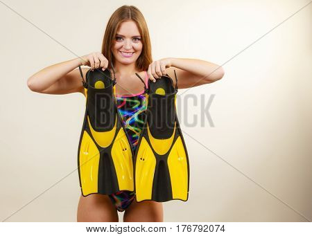 Woman wearing swimsuit holding flippers having fun studio shot on grey. Happy joyful girl dreaming about summer vacation. Snorkeling swimming concept