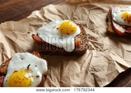 Toasts with fried eggs and bacon on parchment
