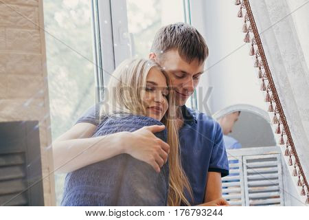 Loving couple sitting on the window loving and gentle look. Positive emotion smiling faces. Couple hugging and looking at each other. A man and a woman love each other