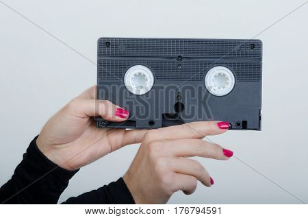woman hands with an old cassette from a videorecorder